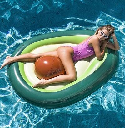 Avocado luchtbed met bal in een zwembad met een vrouw erop.