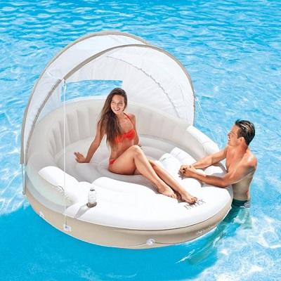 Opblaasbaar lounge eiland met zonnescherm in het zwembad. Op het eiland zit een vrouw en naast het eiland staat een man in het water.