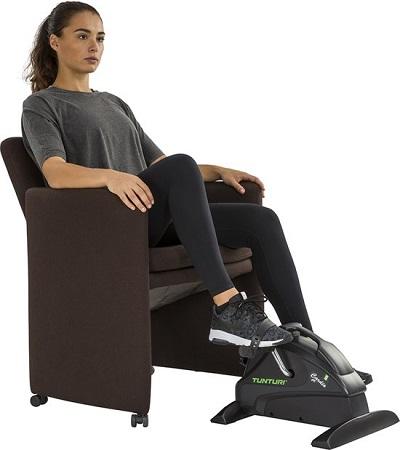 Vrouw op een stoel met een stoelfiets/bewegingstrainer.
