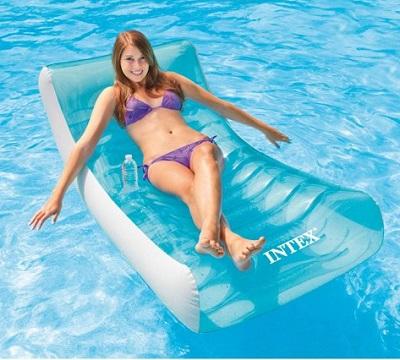 Vrouw op een lounge luchtbed in het zwembad.