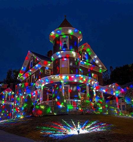 Feestverlichting LED projector voor buiten die een groot huis kleurrijk verlicht.