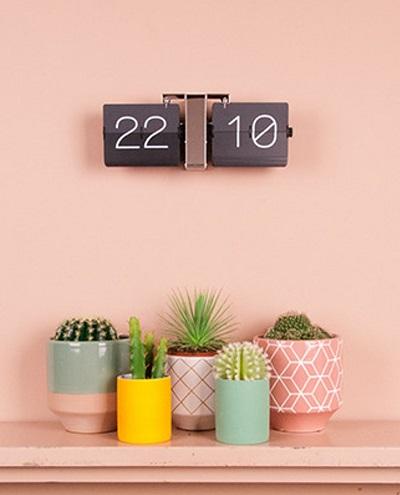 flip klok aan een roze muur boven plantjes in felgekleurde potjes.