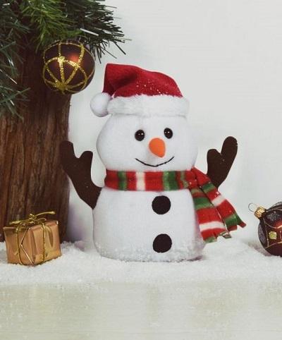 Pratende sneeuwpop bij een kerstboom met een cadeautje ernaast.
