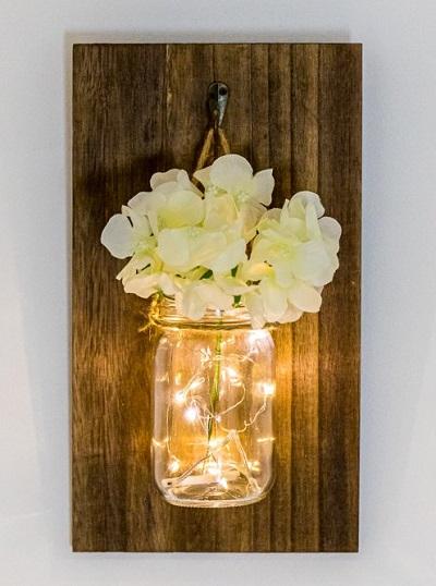 Sfeervolle wanddecoratie die bestaat uit een glazen pot met een witte hortensia en warm-witte LED lampjes tegen een houten achtergrond.