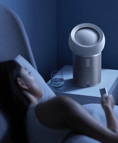 Persoonlijke luchtreinigingsventilator op een nachtkastje in een slaapkamer.