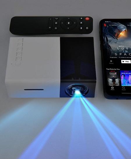 Mini projector met ingebouwde speaker die zowel op je telefoon als je gameconsole kan worden aangesloten.