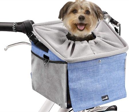 Honden fietstas aan het stuur van een fiets met een hondje erin.