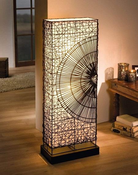 Staande vloerlamp met een gevlochten rotan frame met het patroon van een zon.