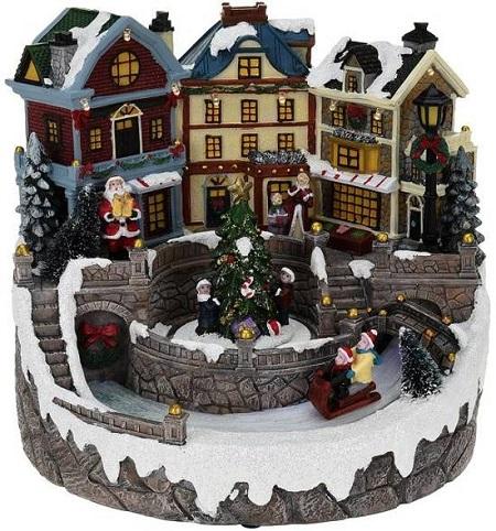 Kerstdorp met verlichte huisjes en sleeënde kinderen.