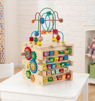 Houten activiteitenkubus op tafel in een speelkamer.