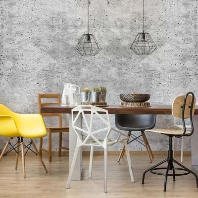 Industrieel fotobehang van een kale betonnen muur met een tafel en stoelen ervoor.