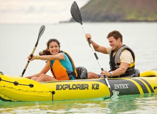 Opblaasbare kayak met een man en een vrouw op een meer.
