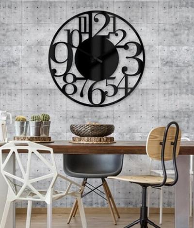 Grote industriële wandklok die aan een grijze muur hangt boven een eettafel met stoelen.