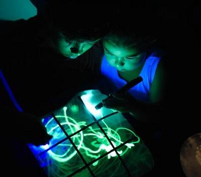 Interactief kussensloop waar twee kinderen met lichtgevende pennen boter-kaas-en-eieren op spelen.