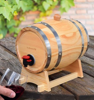 Mini houten wijnvat met een tapkraantje dat op tafel staat terwijl iemand een glas wijn vult.