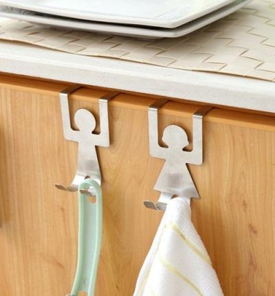 Handdoekhaakjes in de vorm van een mannetje en vrouwtje die aan een kastdeurtje hangen.