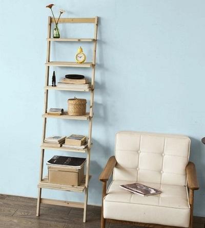 Ladderkast met 6 planken die tegen een blauwe muur staat naast een stoel.