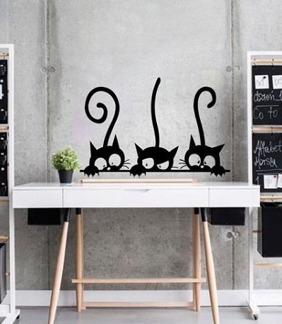 Grappige muursticker van drie katten die nieuwsgierig over de rand van een tafel kijken.