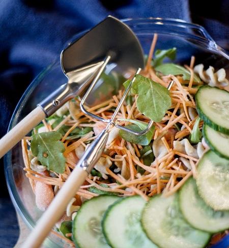 Boerderij slabestek set bestaande uit een mini hooivork en schop in een kom salade.
