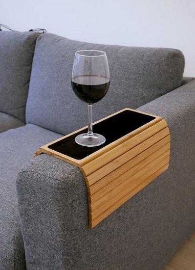 Flexibel armleuning dienblad over de leuning van een bank met een glas wijn.
