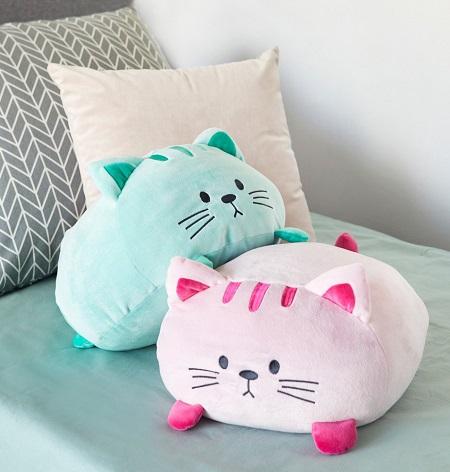 Twee katten kussentjes, roze en blauw, op een bank.