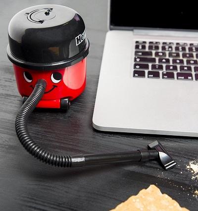 Mini bureau stofzuiger naast een laptop met kruimels op de voorgrond.