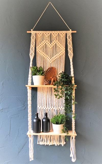 Macramé wanddecoratie en plantenhanger met plantjes.