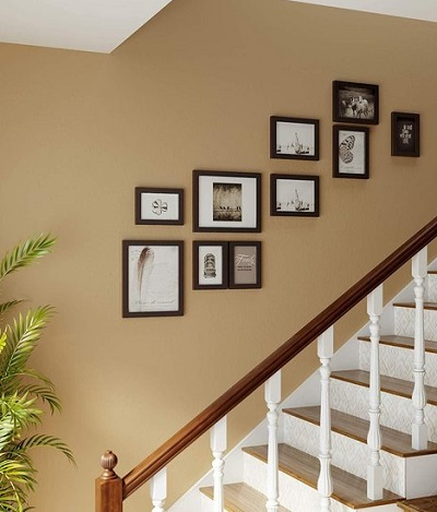 Fotowand met tien lijsten boven een trap.