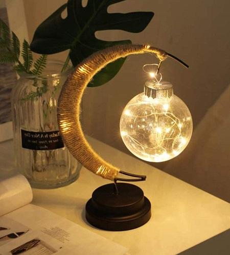 Moon Ball LED tafellampje op een nachtkastje.