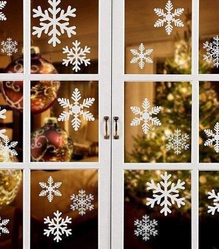 Kerst raamstickers in de vorm van sneeuwvlokken op een raam.