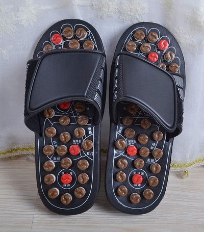 Voetmassage slippers met noppen die reflexologie acupressuurpunten stimuleren.