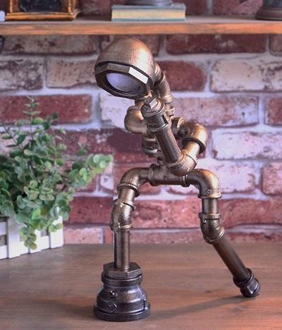 Industriële tafellamp van waterleidingen in de vorm van een rennend mannetje.