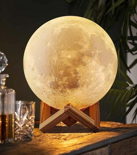 3D geprinte maanlamp met ingebouwde Bluetooth speaker op een houten standaard.